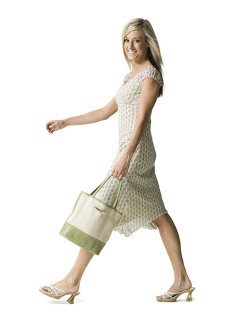 Portrait Of A Young Woman Walking With A Purse