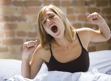 Close-Up Of A Young Woman Sitting On A Bed Yawning