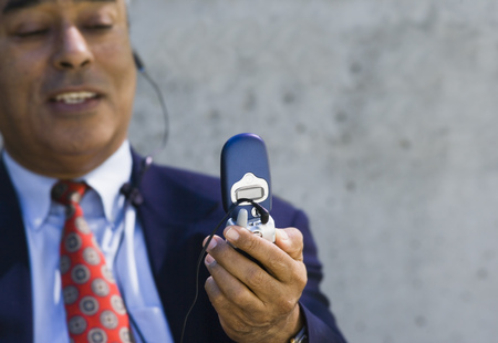 handsfree telephones: Close-Up Of A Businessman Looking At A Mobile Phone LANG_EVOIMAGES