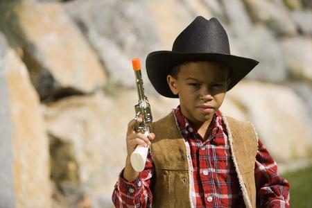 Portrait Of A Boy In A Cowboy Costume Holding A Toy Gun