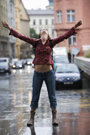 Teenage Girl Standing On A Wet Street And Looking Up