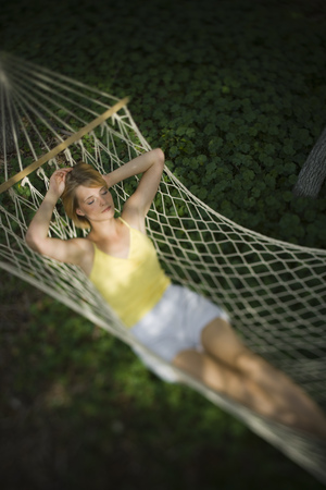High Angle View Of A Young Woman Relaxing In A Hammock LANG_EVOIMAGES