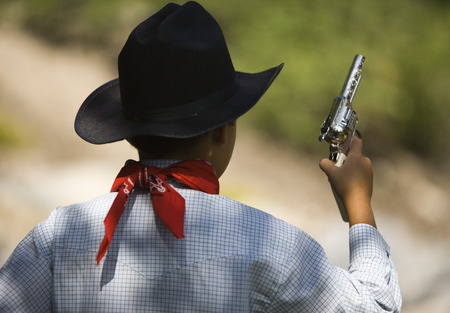 Rear View Of A Boy In A Cowboy Costume Holding A Toy Gun LANG_EVOIMAGES