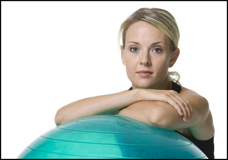 Portrait Of A Young Woman Leaning On A Fitness Ball