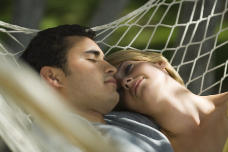 Close-Up Of A Young Couple Sleeping In A Hammock