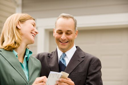 chequera: Close-Up Of A Businessman And A Businesswoman Laughing LANG_EVOIMAGES