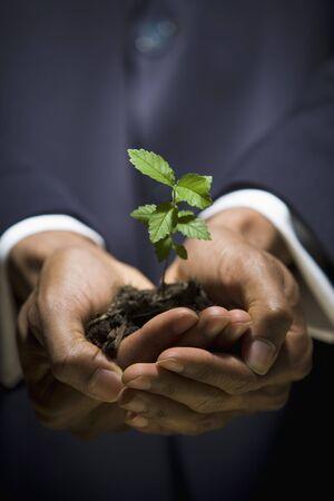 generosidad: Hombre que sostiene un árbol joven LANG_EVOIMAGES