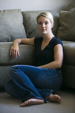 living room sofa: Portrait Of A Young Woman Sitting On The Living Room Floor LANG_EVOIMAGES