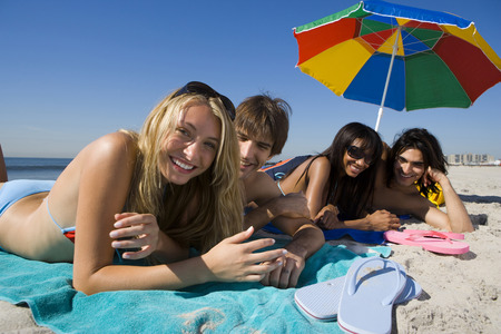 flip flops: Portrait Of Four Young People Lying On The Beach