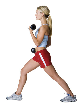 Profile Of A Young Woman Exercising With Dumbbells