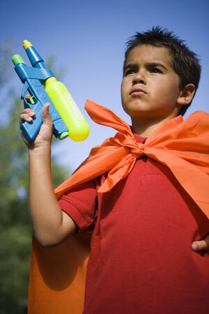 shooters: Low Angle View Of A Boy Holding A Squirt Gun LANG_EVOIMAGES