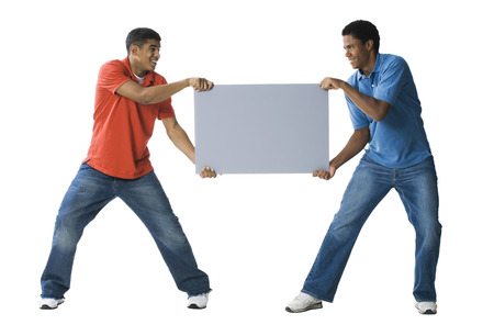 Two Young Men Fighting Over A Blank Sign