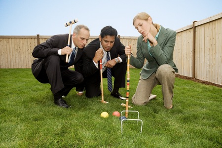 agachado: Two Businessmen And A Businesswoman Playing Croquet