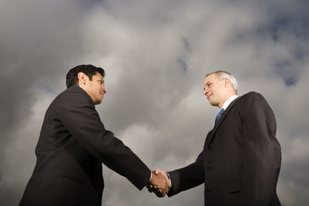 introductions: Low Angle View Of Two Businessmen Shaking Hands