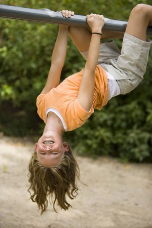 Portrait Of A Girl Hanging Upside Down From A Jungle Gym