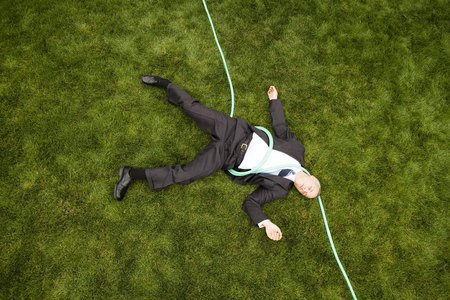 High Angle View Of A Businessman With A Hose Lying Down On A Lawn LANG_EVOIMAGES