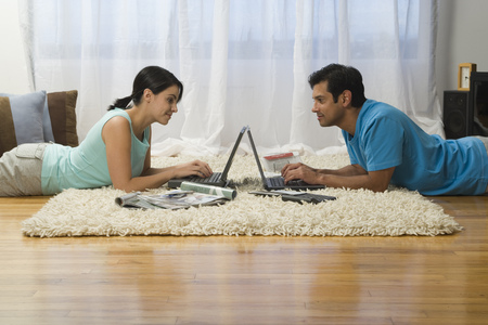 Profile Of A Mature Man And A Mid Adult Woman Working On Laptops