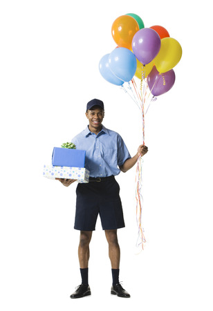 Young Man Carrying Gift Boxes While Holding Balloons