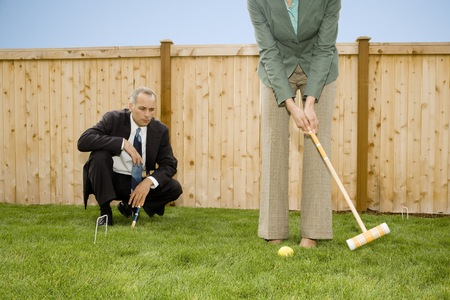 Businessman And A Businesswoman Playing Croquet