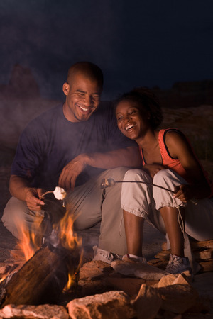honeymooner: Young Couple Sitting By A Campfire