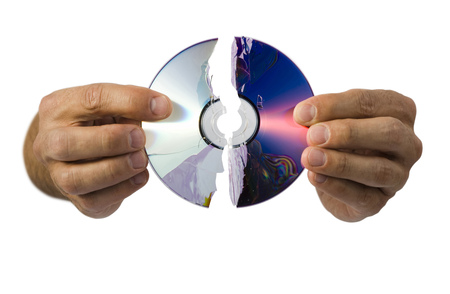 Close-Up Of A Broken Compact Disk In A ManS Hand