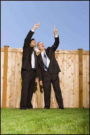 Low Angle View Of Two Businessmen Pointing At The Sky
