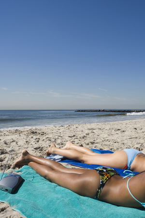 Profile Of Two Young Women Sunbathing On The Beach LANG_EVOIMAGES