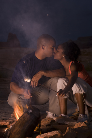 honeymooner: Young Couple Kissing By A Campfire LANG_EVOIMAGES