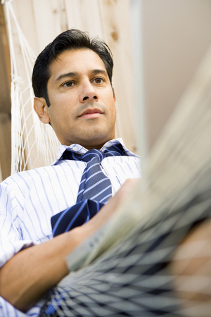 Close-Up Of A Businessman Sitting In A Hammock