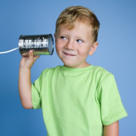 caucasian appearance: Close-Up Of A Boy Holding A Tin Can Phone To His Ear
