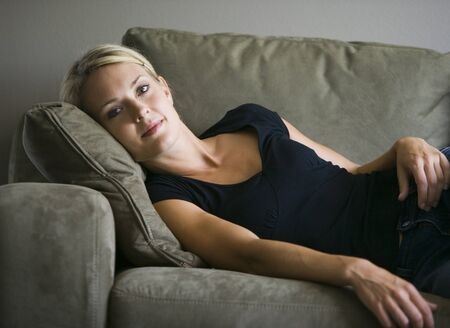 living room sofa: Portrait Of A Young Woman Lying Down On A Couch