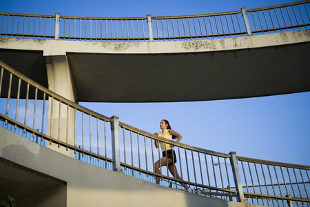 Low Angle View Of A Woman Running On A Bridge