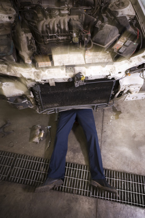 impact wrench: High Angle View Of A Mechanic Repairing A Car LANG_EVOIMAGES
