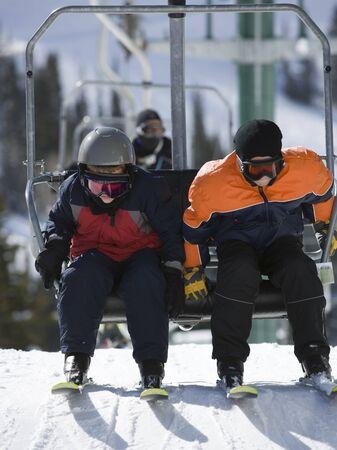 kids at the ski lift: Close-Up Of Two Children Sitting On A Ski Lift