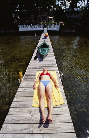 High Angle View Of A Young Woman Lying On A Pier
