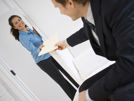 Businessman Giving Documents To A Businesswoman LANG_EVOIMAGES