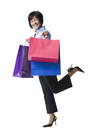 Portrait Of A Mid Adult Woman Standing On One Leg And Holding Shopping Bags