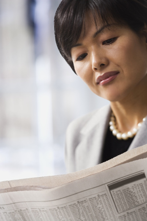 Close-Up Of A Woman Reading A Newspaper LANG_EVOIMAGES