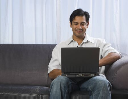 Man Sitting On A Sofa And Using A Laptop LANG_EVOIMAGES