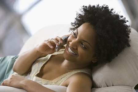 living room sofa: Close-Up Of A Young Woman Talking On A Mobile Phone LANG_EVOIMAGES