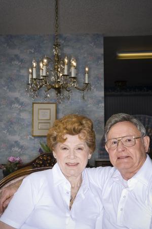 living room sofa: Portrait Of A Senior Couple Smiling LANG_EVOIMAGES