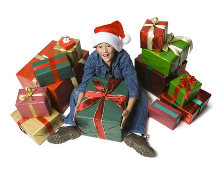 High Angle View Of A Boy Sitting On The Floor With Christmas Presents Around Him
