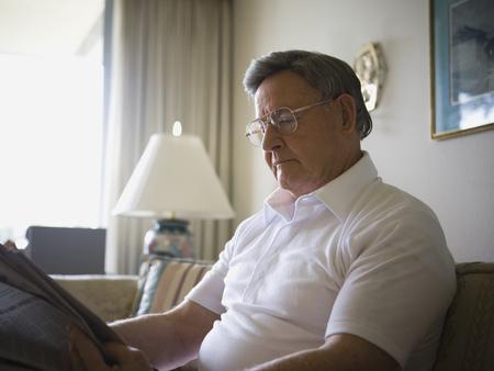 living room sofa: Close-Up Of A Senior Man Reading A Newspaper LANG_EVOIMAGES