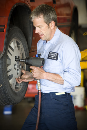 impact wrench: Profile Of A Mechanic Fixing Tire With A Power Tool