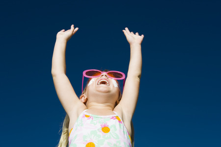 Low Angle View Of A Girl Laughing With Her Arms Raised