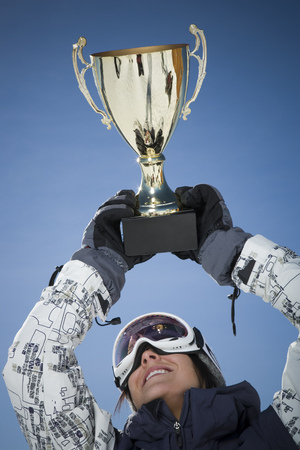 Low Angle View Of A Young Woman Holding Up A Trophy LANG_EVOIMAGES