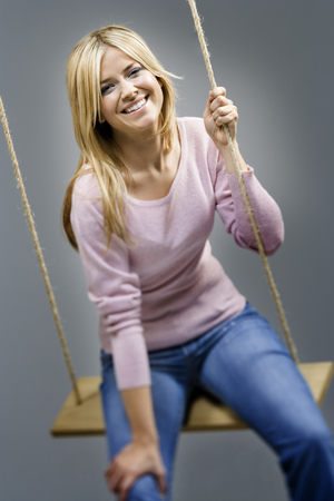 Portrait Of A Young Woman Sitting On A Rope Swing And Smiling