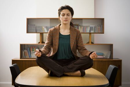 Young Woman Meditating On A Meeting Table