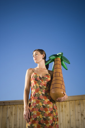 Low Angle View Of A Woman Holding A Plastic Palm Tree