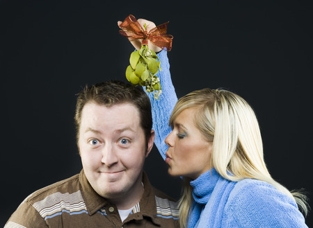 generosa: Close-Up Of A Young Woman Holding A Mistletoe Over The Head Of A Young Man LANG_EVOIMAGES